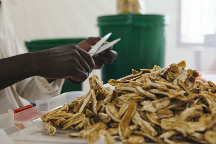 Midsection of man cutting dried bananas
