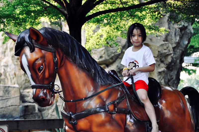 Portrait of a smiling young woman riding horse
