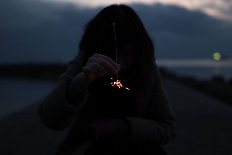 Woman Holding Sparklers While Standing On Pier At Dusk