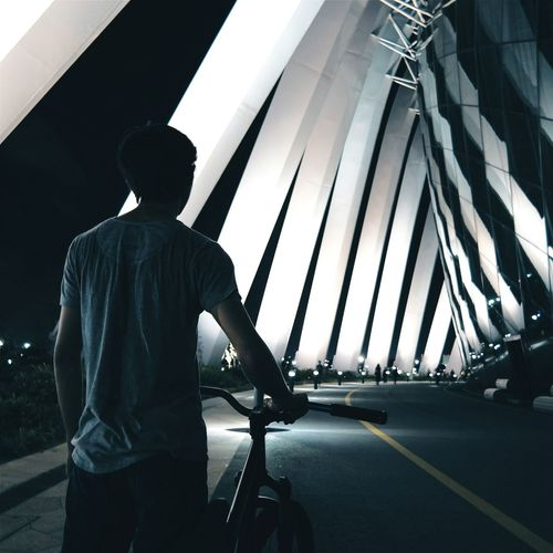 Rear view of man standing with bicycle on illuminated bridge at night
