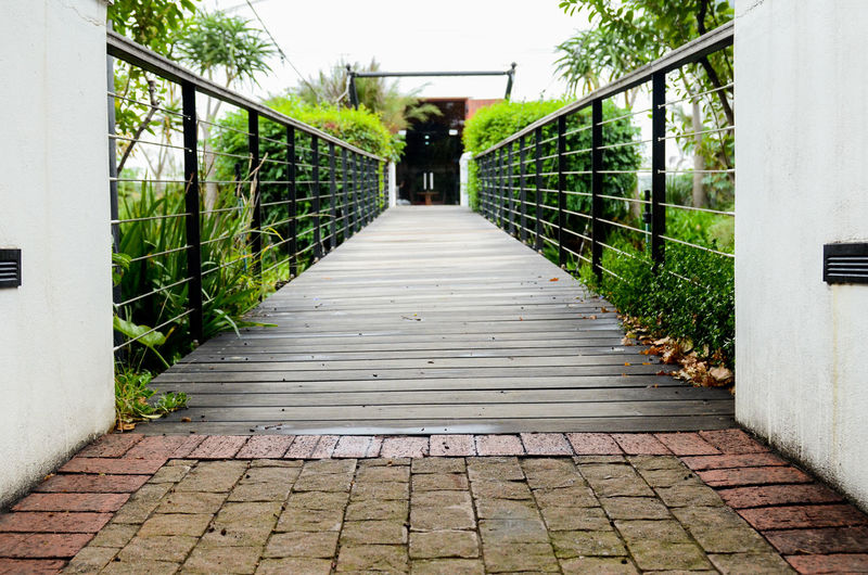 Path Architecture Bridge Built Structure Connection Day Diminishing Perspective Direction Empty Footbridge Footpath Long Narrow Nature No People Outdoors Paving Stone Plant Railing The Way Forward Tree