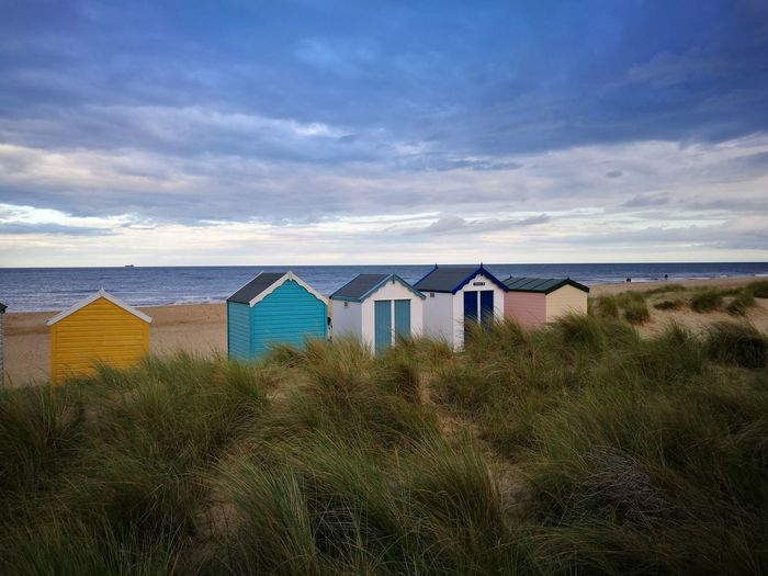 Huts on grassy beach against cloudy sky