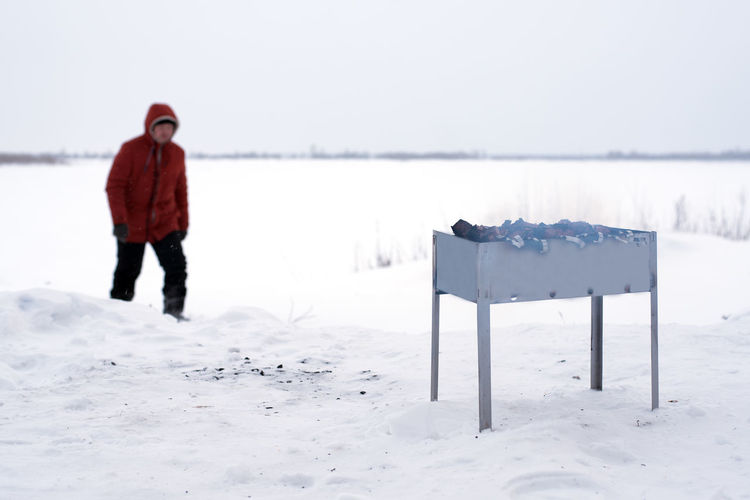 Man walking with barbeque grill on snow covered land against sky