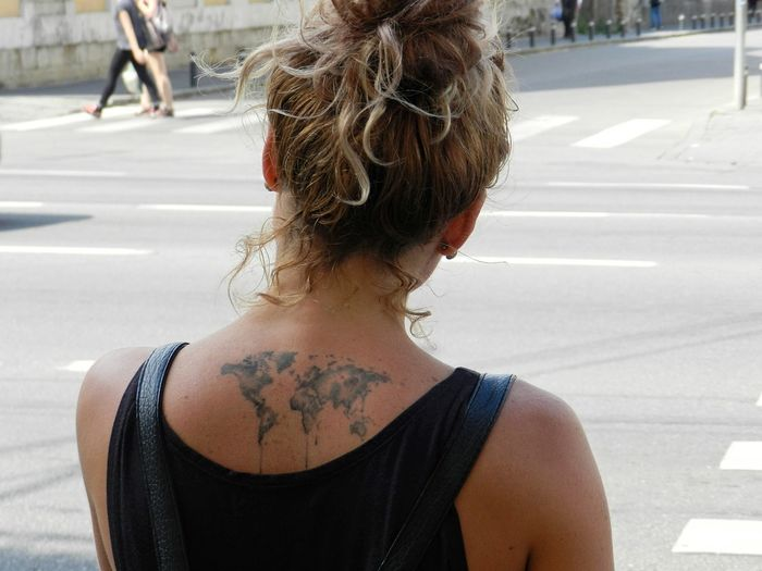 Rear View Of Woman With World Map Tattoo On Back