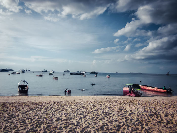 Sandy Beach and Boats Water Sky Sea Cloud - Sky Nautical Vessel Transportation Boat Unrecognizable People Beauty In Nature Scenics - Nature Mode Of Transportation Beach Recreational Pursuit Leisure Activity Cloudscape Tranquil Scene Horizon Over Water Sailboat