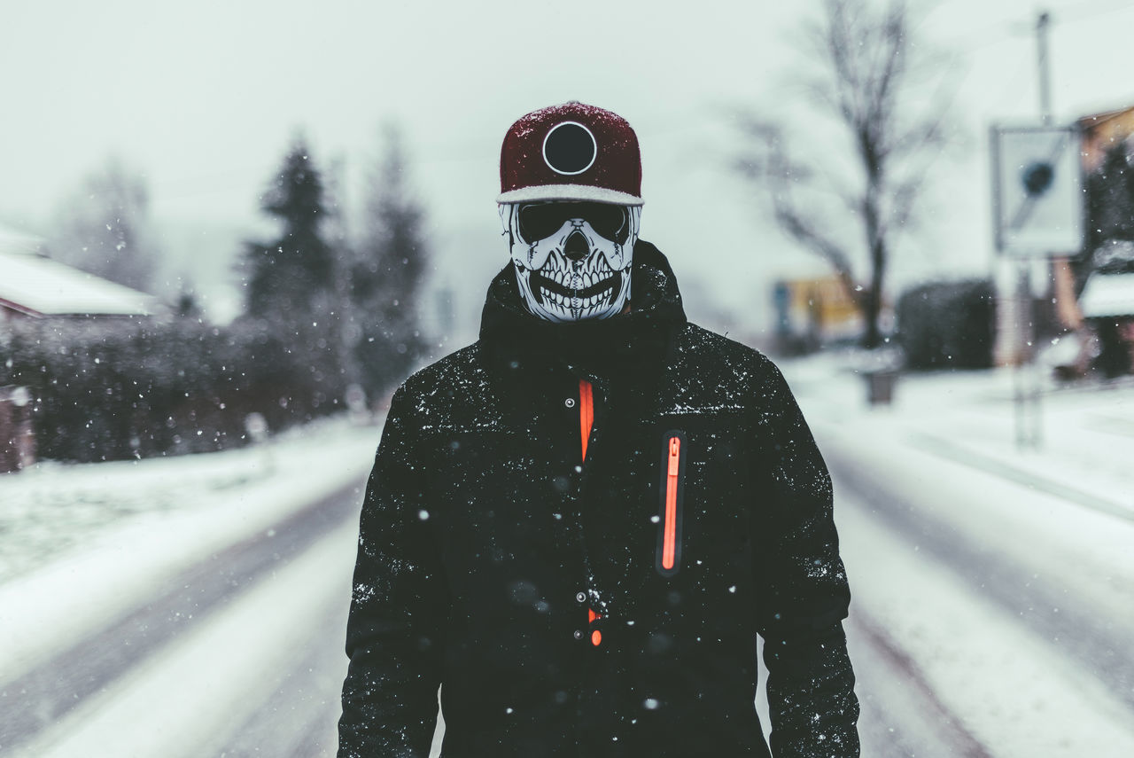 Person wearing mask and standing on snow covered street