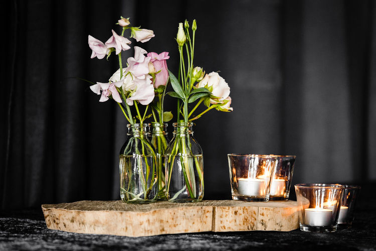Flower vase with lit tea light candles on table