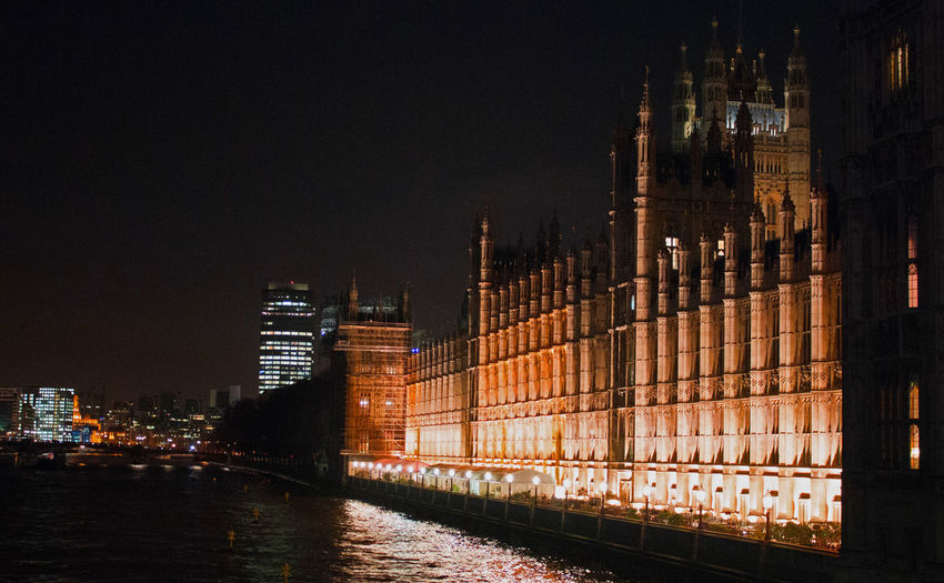 Illuminated houses of parliament by thames river against sky