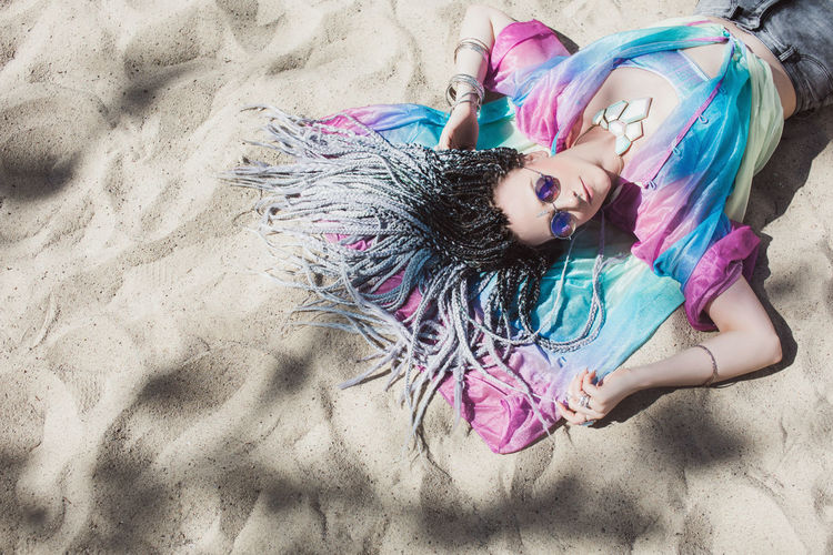 Beautiful expressive fashion forward woman with braided hair laying on the ground Cool Dresses Hair Young Beach Beautiful Woman Colorful Hairstyle Holographic Jewelry Lifestyles Lying Down Lying On Back Neon Outfit Real People Relaxation Sand Sun Sunglasses Women Young Adult