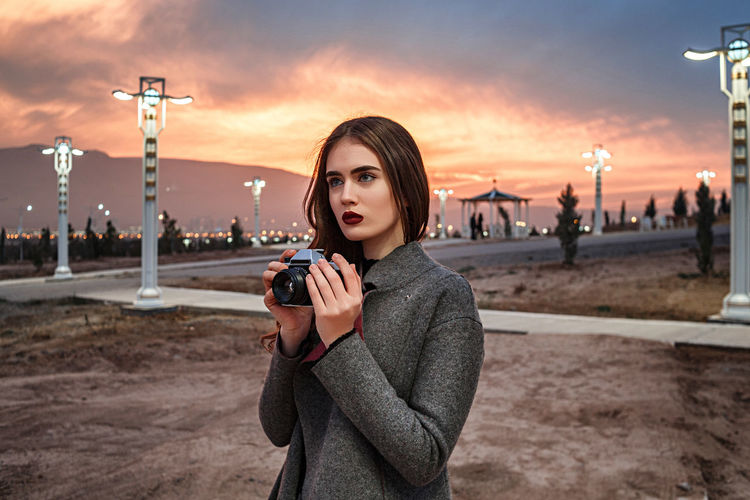 Portrait of young woman photographing against sky during sunset