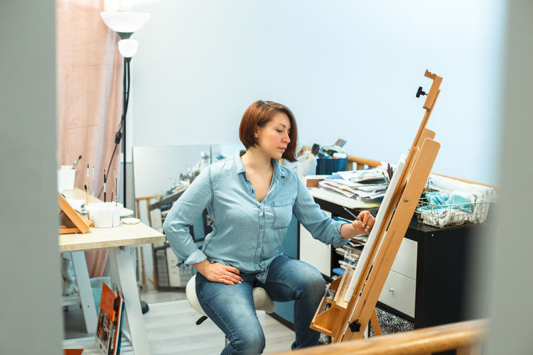 Concentrated middle age caucasian woman artist drawing with pencil on canvas at home art studio