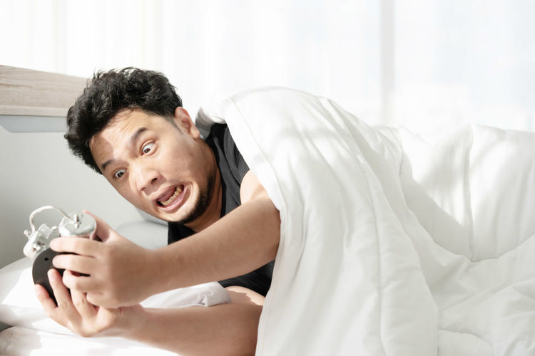 Portrait of a smiling young man holding while relaxing on bed
