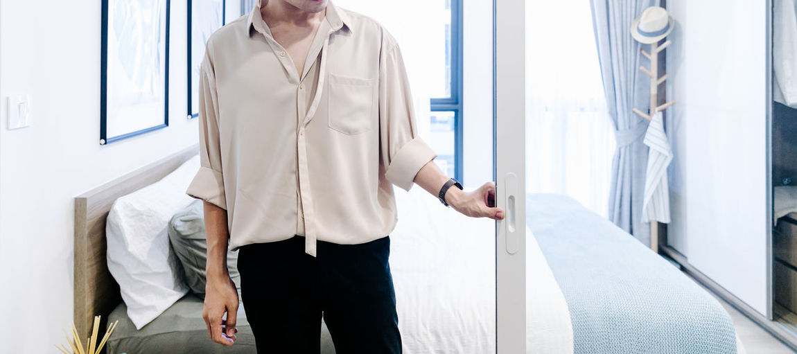 Midsection of man looking through window