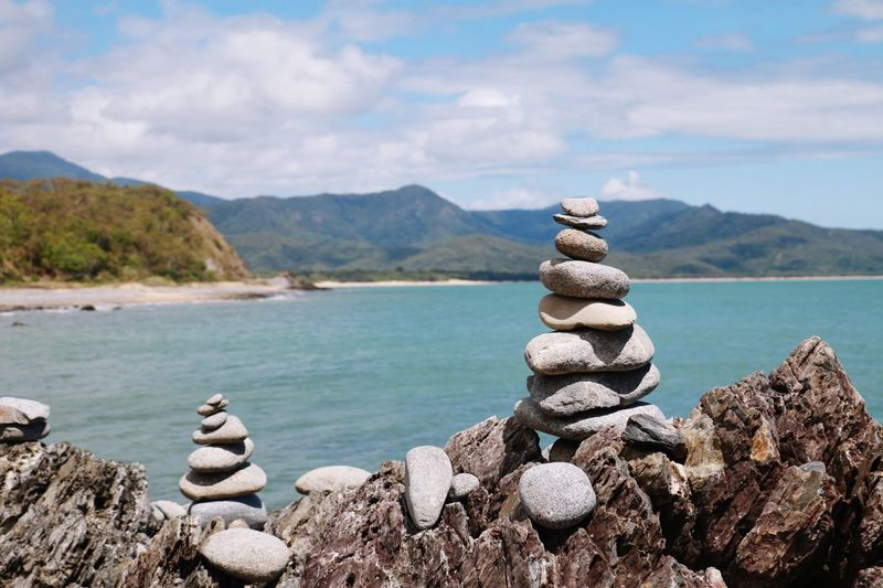 Stack of stones on rocks by sea against sky