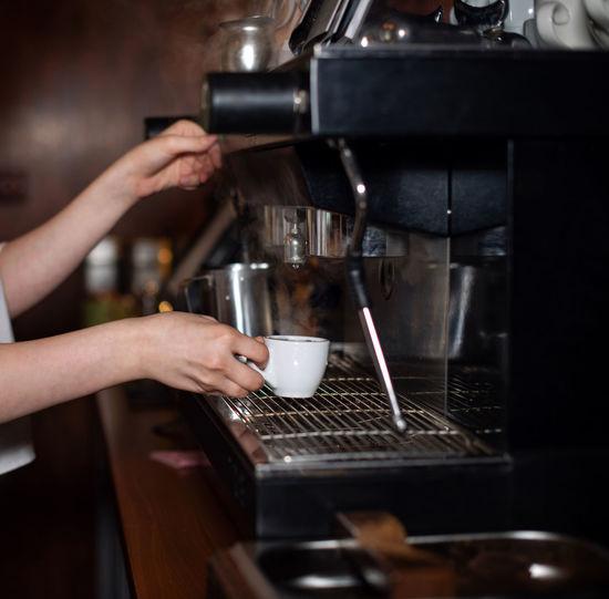 Girl makes espresso in a coffee machine. barista is making coffee. coffee shop, restaurant. espresso