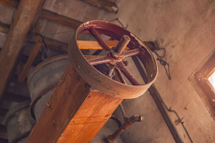 Low angle view of steering wheel in ship