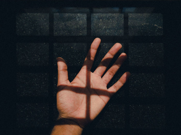 Close-up of hand touching shadow on wall