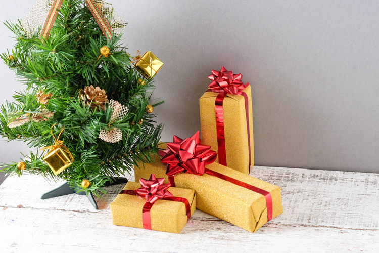 Close-up of christmas tree and presents against gray wall