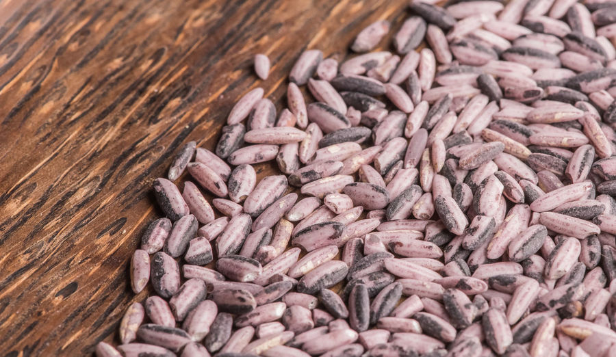 Raw red rice on a dark wooden plate, top view.