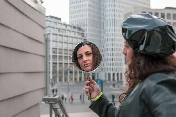 Portrait of woman holding mirror in city