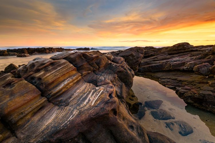 Sunset in Sawarna Indonesia with red sandstone in the foreground Sky Sunset Beauty In Nature Cloud - Sky Rock Scenics - Nature Rock - Object Tranquility Tranquil Scene Solid Orange Color Land Nature Idyllic Non-urban Scene Rock Formation No People Water Beach Outdoors Eroded Red Sandstone Rock Formation Geology