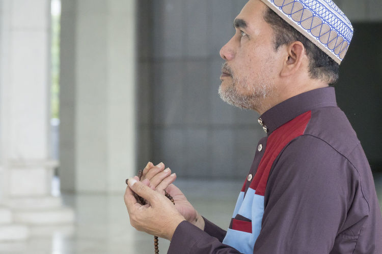 Side View Of Mature Man Praying While Kneeling At Mosque
