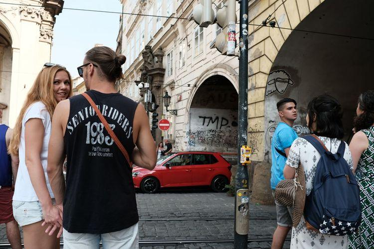 Rear view of people standing on street against buildings