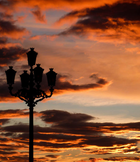 Low angle view of silhouette lamp post against cloudy sky during sunset