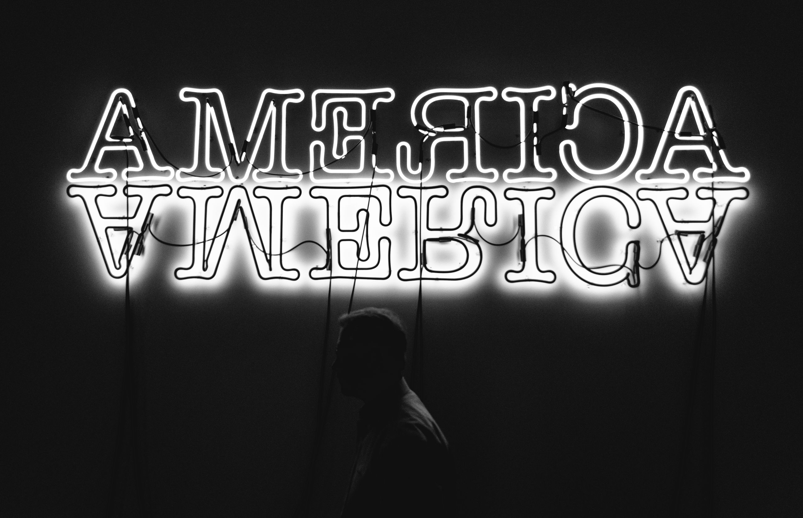 text, illuminated, western script, communication, night, neon, lighting equipment, indoors, real people, glowing, one person, standing, sign, capital letter, electricity, dark, lifestyles, leisure activity, men, black background, light
