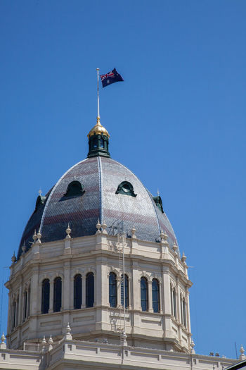 Low angle view of royal exhibition building dome against clear blue sky