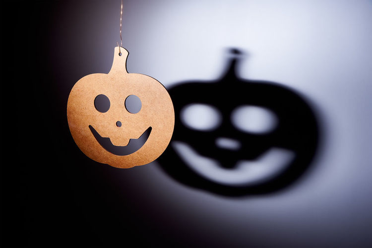 Wooden pumpkin decoration hanging against shadow on wall during halloween