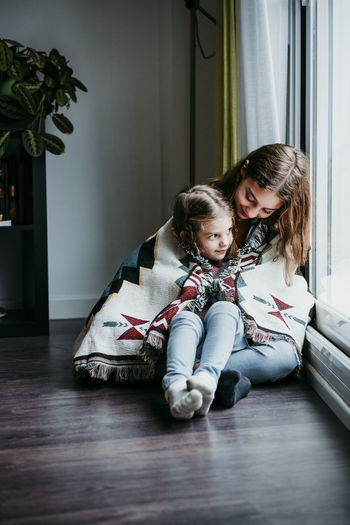 Mother and girl sitting on floor at home