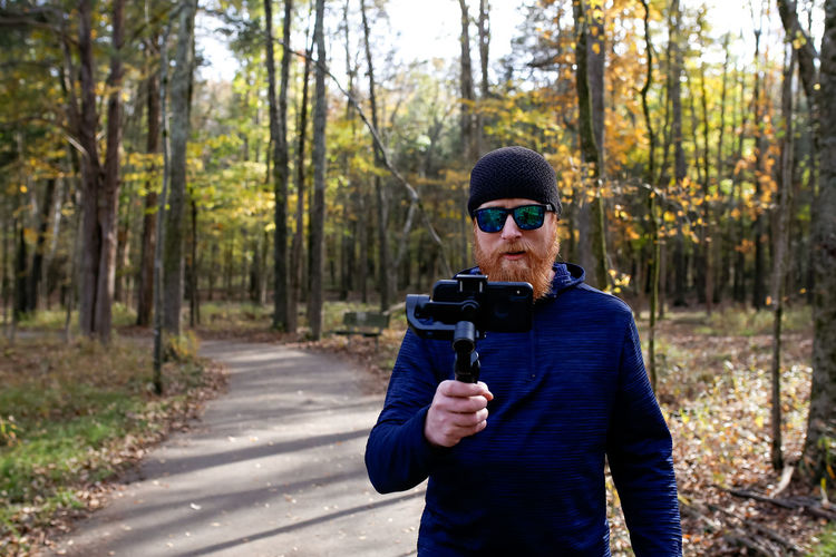 Man on nature hike using a gimbal and mobile phone for photography Phone Photography Mobile Phone Photography Gimbal Nature Hike Nature Photography Autumn colors Autumn Fall Fall Colors Nature Walk ♥ Nature Trail WoodLand Outdoors Real People One Person Tree Leisure Activity Forest Waist Up Front View Photography