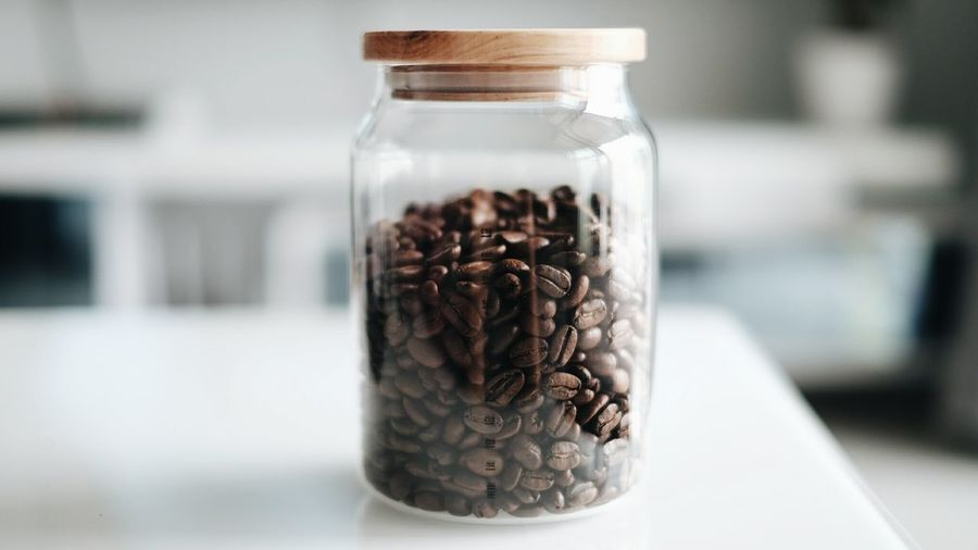 Close-up of roasted coffee beans in jar on table