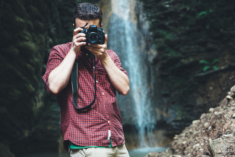Man photographing through digital camera against waterfall
