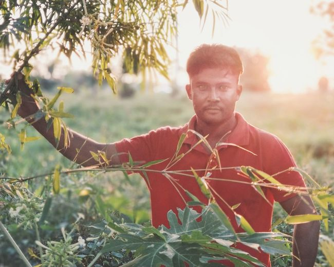 Portrait of mid adult man standing by plants during sunset