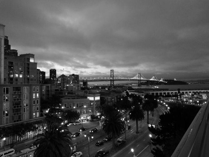 Illuminated city by bay against cloudy sky
