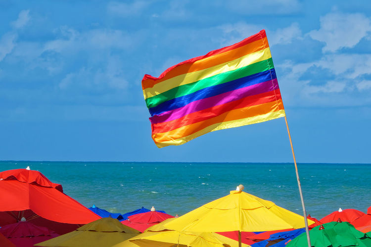 Multi colored flag on beach against sky