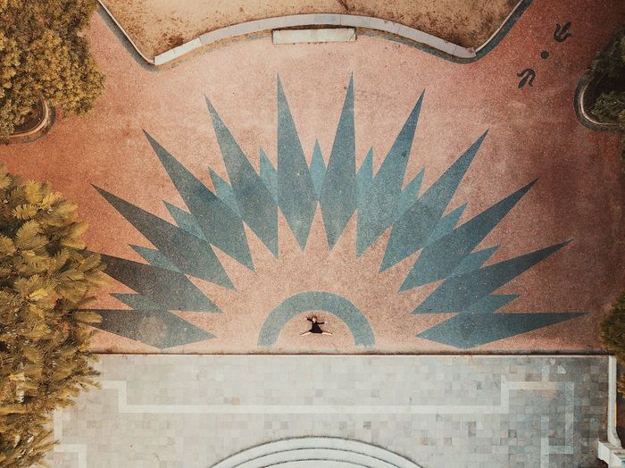 Aerial shot of female dancer in urban plaza setting with geometric pattern