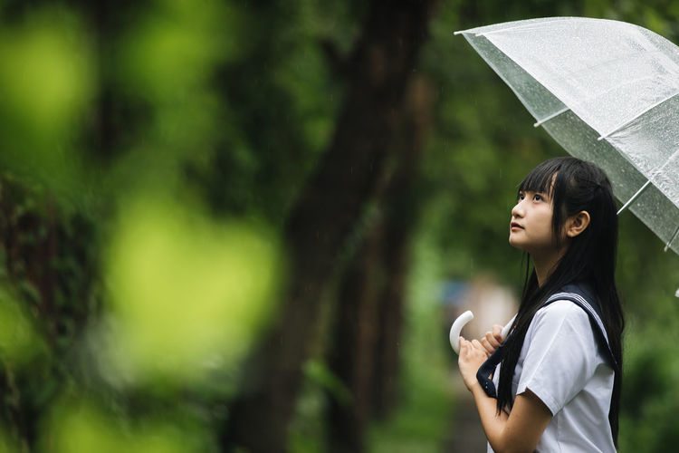 Young student with umbrella standing in park