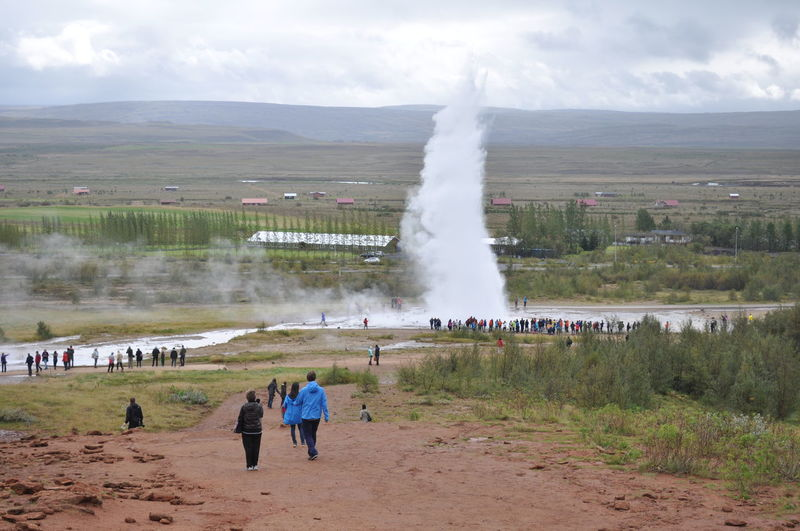 Tourists visiting famous geyser against sky