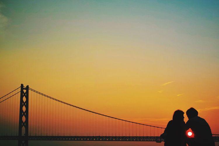 Silhouette Couple And Akashi Kaikyo Bridge Against Sky During Sunset