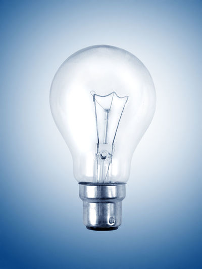 Close-up of light bulb against colored background