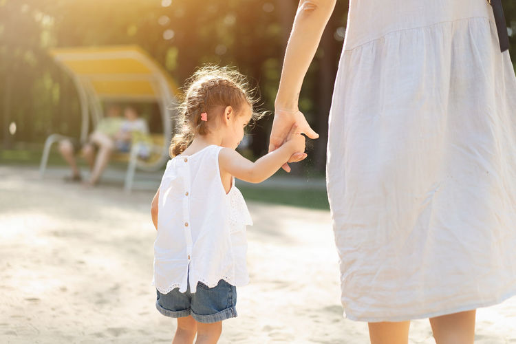 Midsection of mother holding hands of daughter