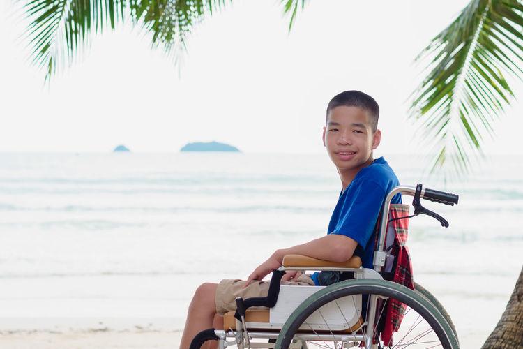 Portrait of boy sitting on wheelchair against sea