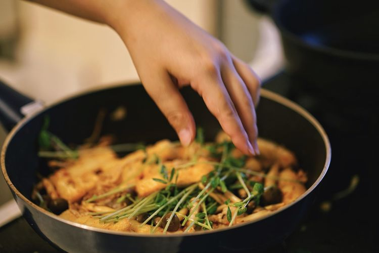 Close-up of hand preparing food in frying pan