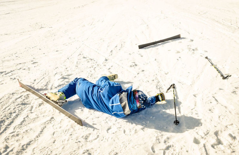 Man falling while skiing on snow