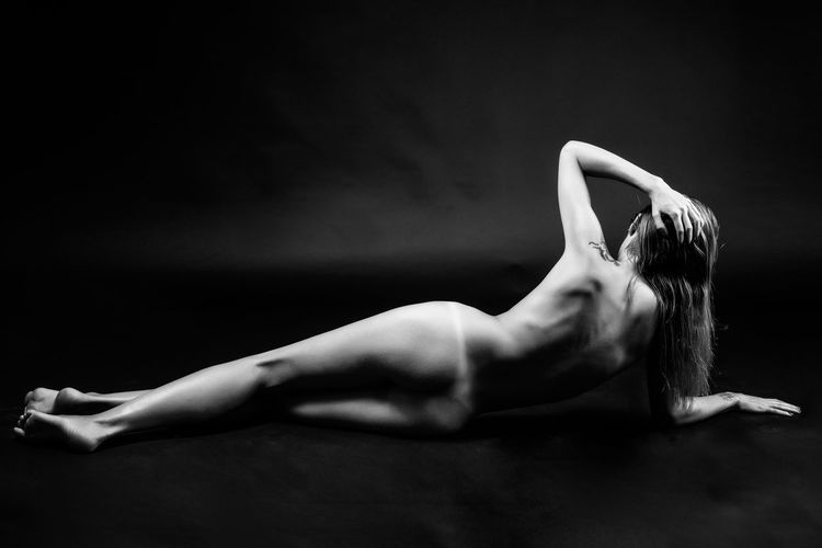 Rear view of naked seductive woman lying on black background