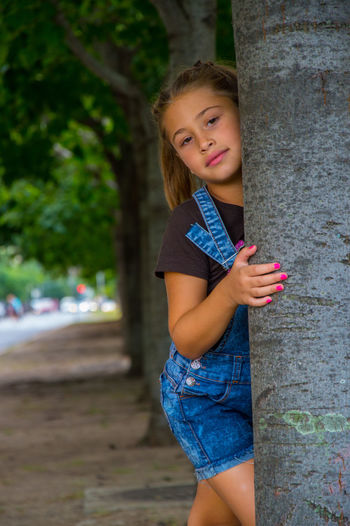 Portrait Of Smiling Girl Leaning On Tree Trunk
