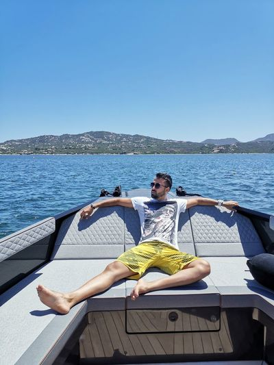 Man relaxing on boat in sea against clear sky